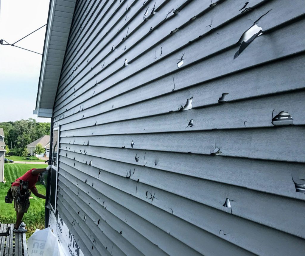 damaged home siding with holes from a severe storm