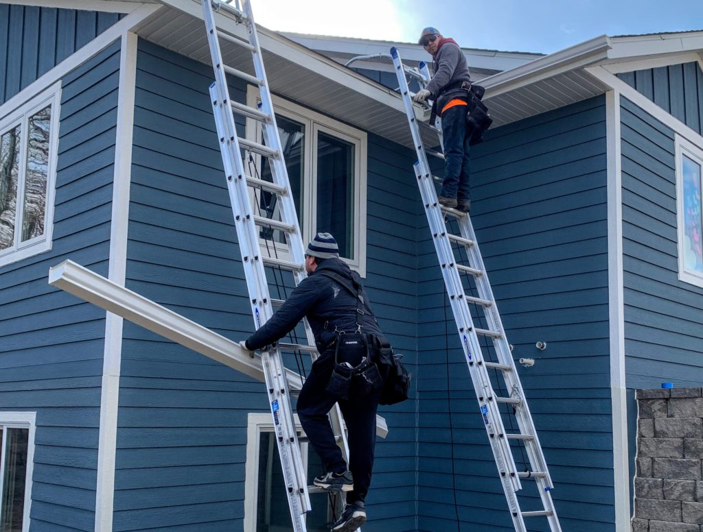 contractor installing replacement gutter on ladder