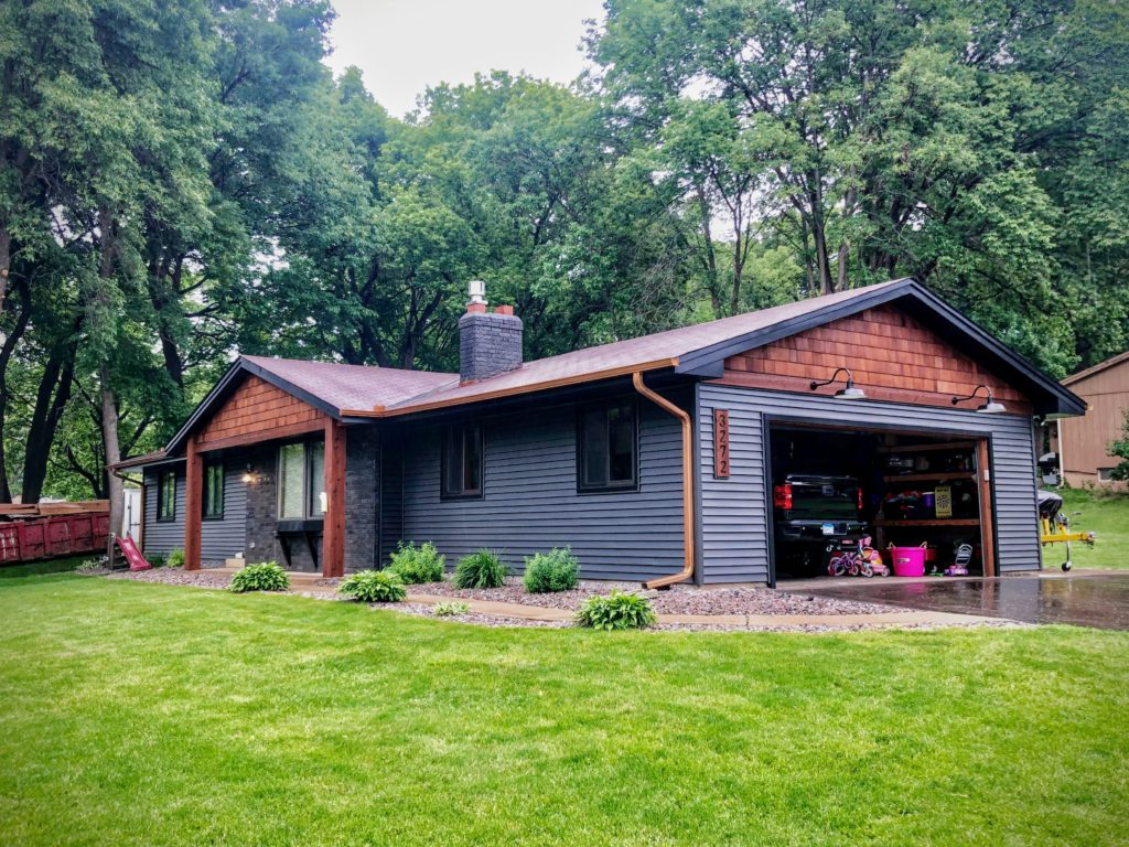 newly-painted house on green hill with wood accent siding