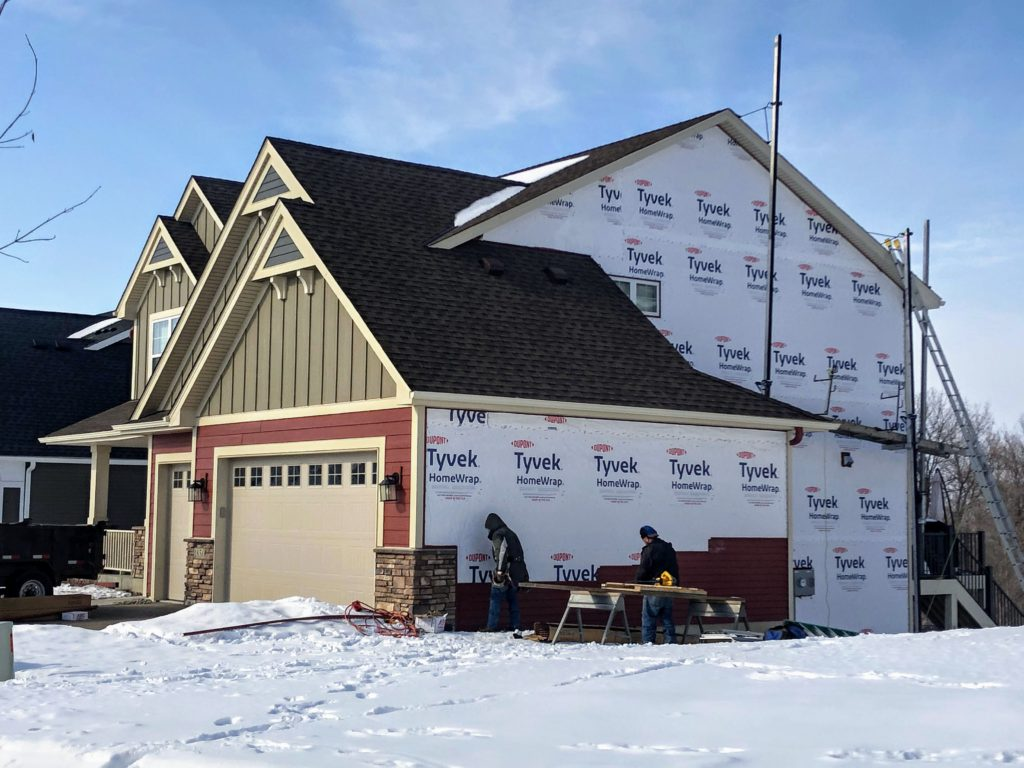 new construction home in the process of having siding installed